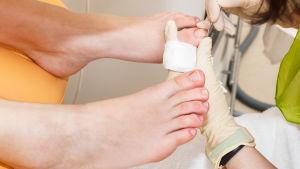 En person med gummihandskar på händerna använder ett litet verktyg för att få bort smuts under tånaglarna.