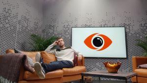 Buster Cj Berg sitter i Big Brother-studion med fötterna raklånga uppe på soffan och huvudet lutar mot vänstra handen. Han tittar upp mot taket. Bredvid honom syns den stora Big Brother-loggan på en tv-skärm.