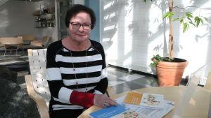 Kvinna med randig tröja sitter vid et bord.