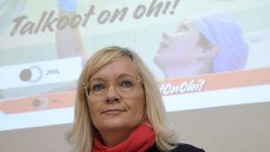 """JHL:s ordförande Päivi Niemi-Laine tittar snett in i kameran. Bakom henne finns en bild av en städare på ett sjukhus med texten """"Talkoot on ohi"""" alltså """"Talkot är slut""""."""