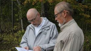 Två män står framför ett skogsparti och tittar på ett papper.