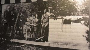 Ett äldre svartvitt fotografi där flera personer står bredvid en spritsläde av trä.