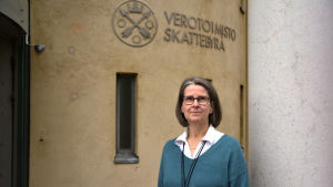 Annette Nyberg poserar framför skatteförvaltningens logotyp.