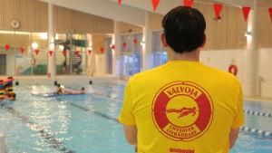 En simövervakare med gul tröja står bredvid en simbassäng.