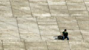 En man som sitter på en stor stentrappa, utomhus i solen,  med en laptop i famnen.