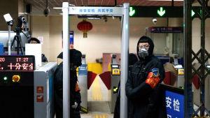Vakter i Pekings metro tar temperaturen vid ingången till en station.