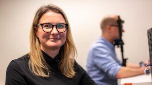 Psykologiforskaren Johanna Kaakinen tittar rakt mot kameran. I bakgrunden syns hennes kollega som lutar hakan mot en ställning. Han gör ett psykologiskt test som bland annat mäter hans pupiller.
