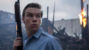 Poliisimies katselee ympärilleen haulikko kädessään elokuvassa Detroit. Taustalla näkyy palava talo.