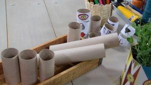 Ett bord med pysselsaker, bland annat tomma pappersrullar och färgpennor.
