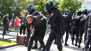 Poliser i Moskva för bort en demonstrant som visat stöd för demonstranterna i Chabarovsk.