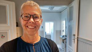 En kvinna med glasögon ler där hon står i en korridor