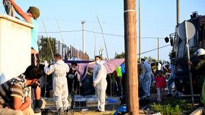 Poliserna var klädda i skyddsdräkter och migranterna fick genomgå coronatest innan de fick komma in i det nya tältlägret på torsdag.