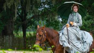 En vit herrgårdsfru inspekterar ägorna till häst.