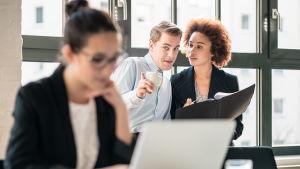 Kvinna sitter vid dator, i balkgrunden en man och kvinna som pekar på henne och viskar