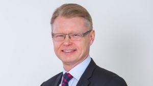 Ett porträtt på Mika Nykänen, vd för HRT. Han har glasögon och ler mot kameran.
