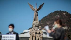 En staty av Fågel Fenix med en staty av en familj med mamma, pappa och ett barn framför.