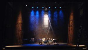 Teaterscen med utsrpidda möbler.