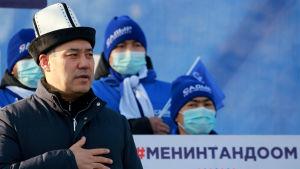 En man iförd en traditionell kirgizisk hatt håller handen mot bröstet.