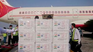Lådor med markeringar som visar att de innehåller vaccin ligger på en lastpall framför ett flygplan med Air Indias beteckningar.