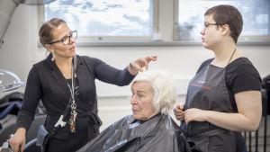 En frisörslärare och en studerande står på var sin sida av en kund och funderar på hennes frisyr.