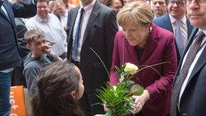 Angela Merkel får blombukett under valtillställning.