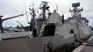 Ett militärfartyg står vid en kaj.