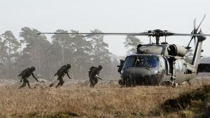 Soldater springer till en helikopter.