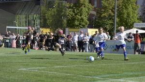 En av FC Komus spelare har nyss sparkat bollen mot målet på Vasa torg. På bilden är hon fångad i luften mitt i ett hopp