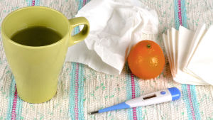 En mugg med te, näsdukar, en clementin och en febertermometer står på en trasmatta.