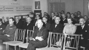 Uppklädda personer sitter på stolrader.