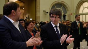 Kataloniens vice president Oriol Junqueras och president Carles Puigdemont applåderar efter undertecknandet av självständighetsdeklarationen.
