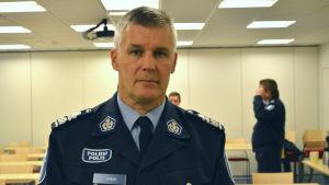 En bild av polischef risto lammi. I bakgrunden i konferensrummet står andra poliser men de är ur fokus.