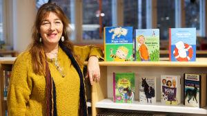 En person (Henrika Andersson) poserar intill en bokhylla och tittar in i kameran.