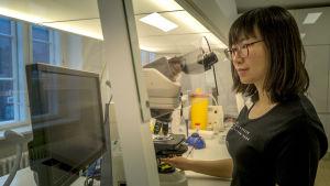 Kvinna undersöker spermier i ett laboratorium med mikroskop och datorskärm.