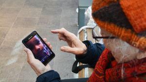 Desiré tittar på bilder från telefon