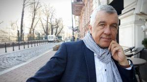 Csaba Csontos står på gatan och lutar sin armbåge mot en husvägg.