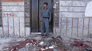 En afghansk polis intill attentatsplatsen i Kabul, där minst 31 människor dödades i ett självmordsattentat på söndagen.
