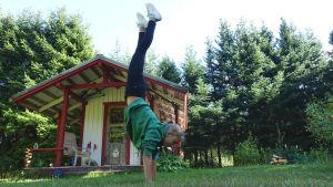 En flicka med starta jeans och en grön huvtröja står på händer på en gräsmatta. Bakom henne står en lekstuga i trä.