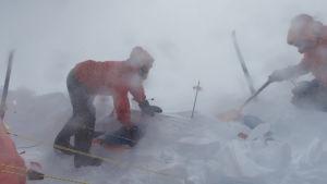 Två personer iklädda röda tjocka jackor och byxor. De befinner sig i ett snölandskap och det är storm. De gräver fram en pulka.