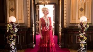 Näyttelijä Mari Perankoski punaisessa pitsineuleasussa vanhanaikaisessa juhlasalissa