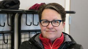 En medelålders kvinna med mörkt kort hår och glasögon.