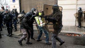 Polisen griper en demonstrant på Champs Élysées på lördag eftermiddag då hundratals andra redan gripits.