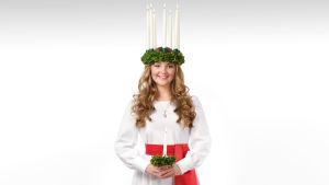 Finlands lucia 2018 Elin Qvist står med luciaklänning och tända ljus i luciakronan.