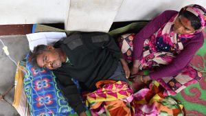 En manlig patient tillsammans med hans fru i sjukhuset i Golaghat på lördagen.