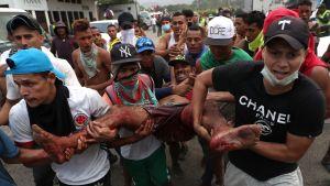 Demonstranter bär en man som skadats i sammandrabbningar vid gränsen mellan Venezuela och Colombia.