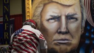 Man i fägrgglad skjorta med USA-flagga beundrar tavla av Donald Trump.