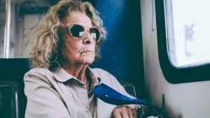 vanha nainen istuu junassa