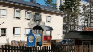 En klätterställning för barn på en gård invid en ljusbeige stenbyggnad som fungerar som skola och daghem.