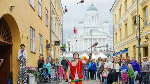 Juggler in front of a small crowd of people. Helsinki Cathedral
