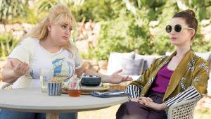 Penny (Rebel Wilson) och Josephine (Anne Hathaway) sitter vid ett bord i trädgården och argumenterar.